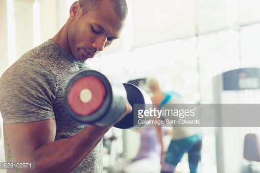 Focused man doing dumbbell biceps curls at gym