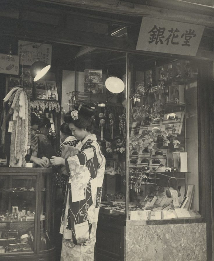 A young maiko, or apprentice geisha, in her formal or holiday dress is purchasing items in a tiny boutique specializing in hair ornaments and similar gewgaws. Her kimono, with very long sleeves, is a prewar style.
