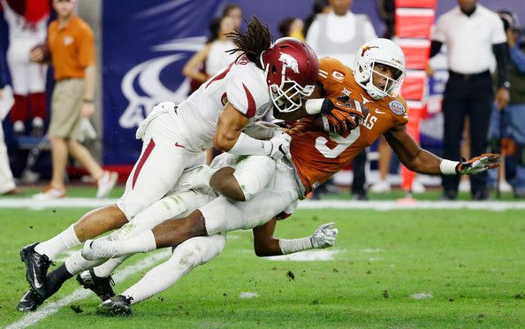 Alan Turner #27 of the Arkansas Razorbacks tackles John Harris #9 of the Texas Longhorns in the first half during their game at the AdvoCare V100 Texas Bowl at NRG Stadium on December 29, 2014 in Houston, Texas. (December 28, 2014 - Source: Scott Halleran/Getty Images North America)