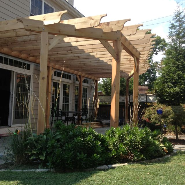 Beautiful cedar pergola in West Chester PA with rounded form using varying length rafters mimicking the shape of the patio on which it sits.  The perfect addition for this town house.