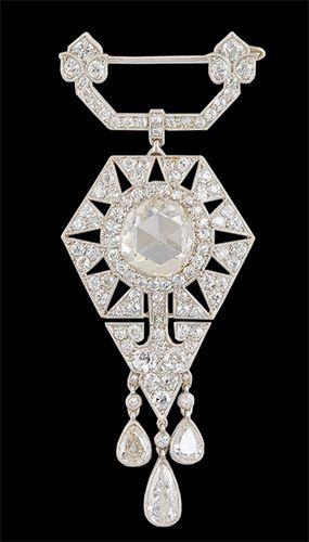 An Art Deco Diamond Pendant Brooch, by Cartier. Set with a rose-cut diamond, within an old European-cut diamond, openwork geometric plaque with three pear shaped diamond pendants, to the old European-cut diamond surmount, mounted inplatinum, Circa 1915, with French assay marks and maker's marks.