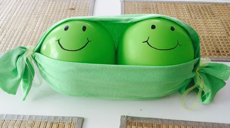 Two Peas in a Pod Baby Shower Decoration! Two green balloons placed inside a piece of green fabric tied with some pretty ribbon :) Super cheap and adorable