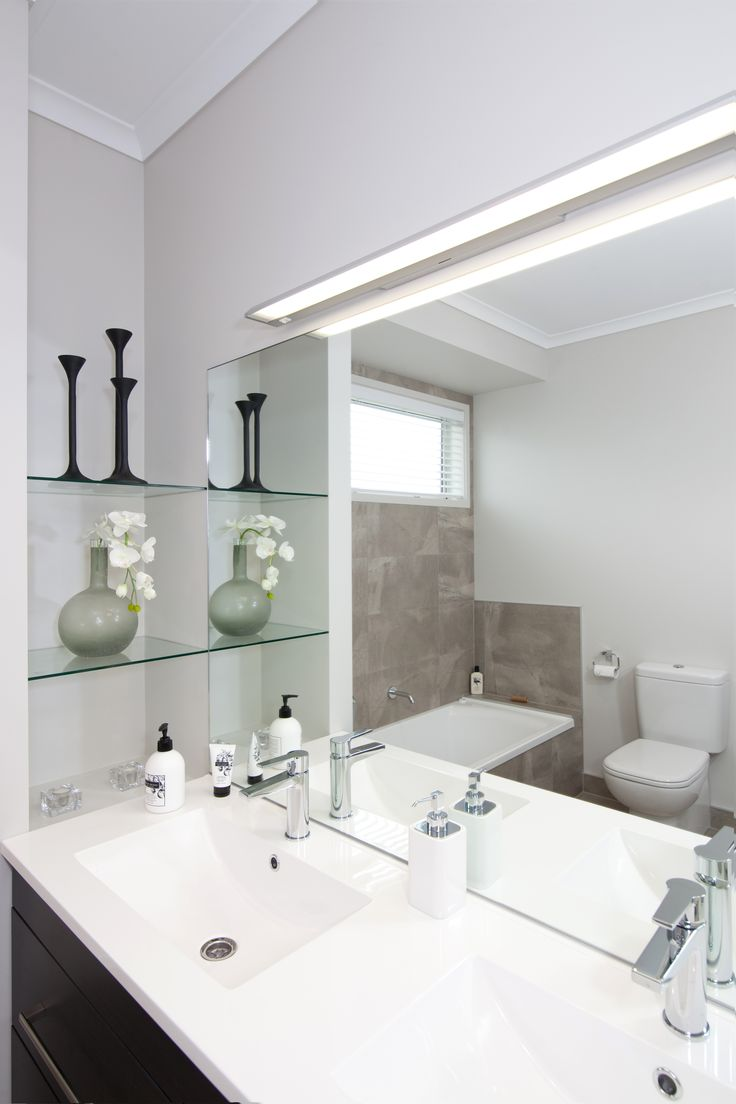 This bathroom includes a stylish glass shelf in the corner between bath and basin. The built-in bath is visible in the mirror reflection.