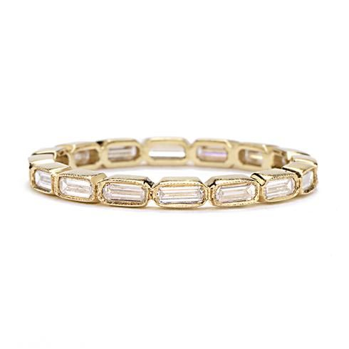 SINGLE STONE BAGUETTE DIAMOND ETERNITY BAND The focus is on the brilliant baguette-shaped diamonds in this streamlined, modern wedding band, handcrafted from yellow gold.   Diamonds:  0.60 total weight (F color, VS1 clarity) Metals:  18k yellow gold Currently available in a size 6.  Other sizes must be special ordered. Handmade in USA
