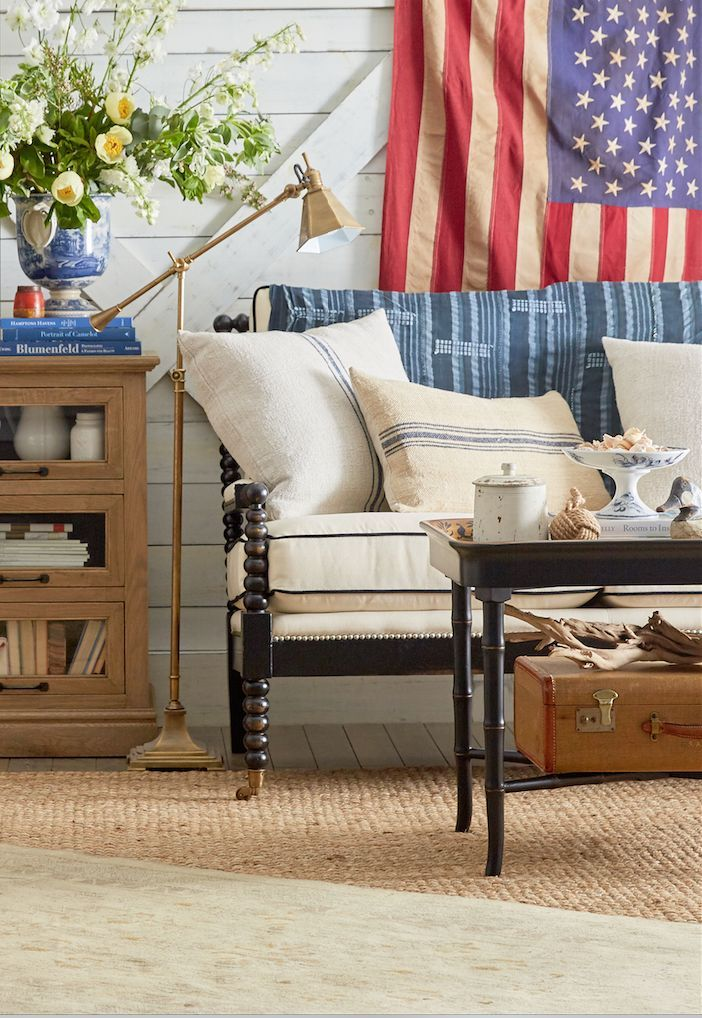 A classic Americana styled living room with a mix of red, white and blue textiles, natural materials and antiqued brass.