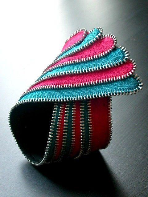 Diseño de la fuente de trenzado rayas lineales, formado en forma de bollo. Hecho de cremalleras azules rojas y verde azuladas con dientes de plata