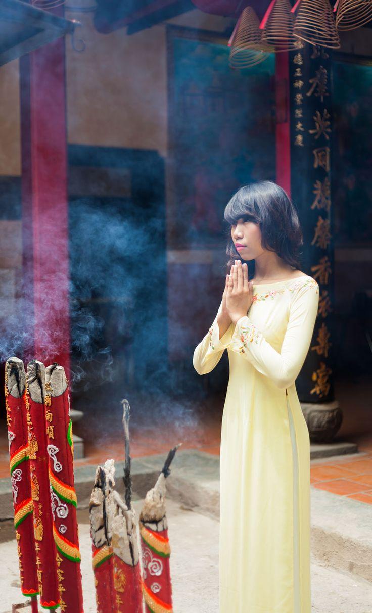 Eine vietnamesische Frau betet in einem chinesischen Tempel.