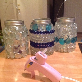 Got a new glue gun at craft night and put it to use! Took a glass jar... Use any size you have around the house. Got some glass stones (they glue better than the glass marbles) and started to glue. Final step add wire if you plan to hang (our amazing craft teacher twisted up for us) add a candle and you have one of a kind patio lighting!!! Love Craft night with the ladies!