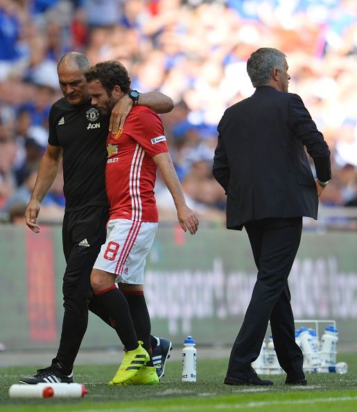 Manchester United's Spanish midfielder Juan Mata talks with Manchester United's Portuguese first team coach Silvino Louro after he is…