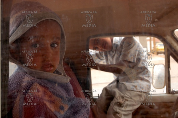 Two children are waiting for their parents inside the car in a street of Adrar