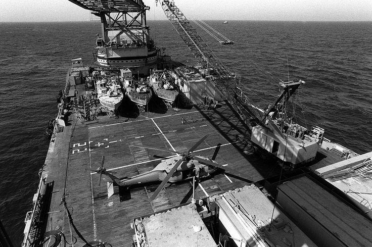 DN-SN-88-10159 - La grúa a bordo de la barcaza Hércules se prepara para levantar una patrullera PB Mark III en el agua para una patrulla. Los patrulleros de aluminio de 65 pies trabajan en parejas para monitorear la actividad de los pequeños botes en el Golfo. Un helicóptero del Ejército de los Estados Unidos UH-60 Blackhawk está especialmente aparcado en la plataforma del helicóptero.
