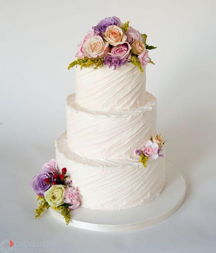Diagonal texture buttercream wedding cake with fresh flowers. A simple but elegant rustic wedding cake.