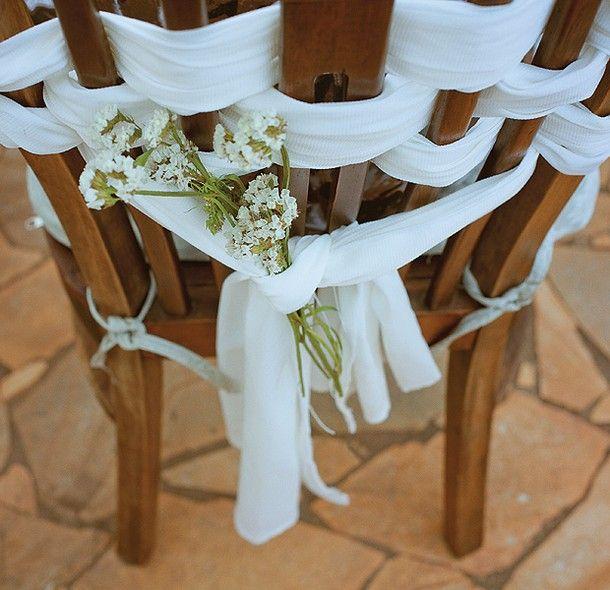 Tiras de tecido enroladas no encosto dão suporte ao pequeno arranjo. Boa pedida para um casamento no jardim