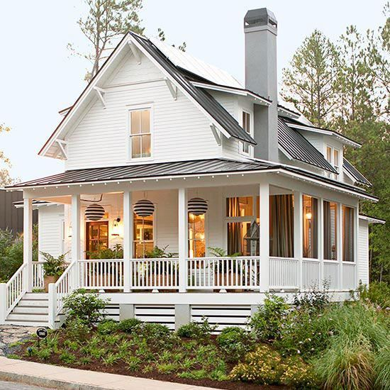 Lovely white cottage with wraparound porch  tin roof.