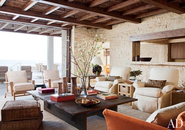 Rough stone walls and exceptional views add drama to the great room of a Southern California house, which was conceived by architects KAA Design and decorated by Atelier AM. The oak-frame armchairs were custom made; the club chairs, upholstered in a Loro Piana linen, are by Hancock & Moore.