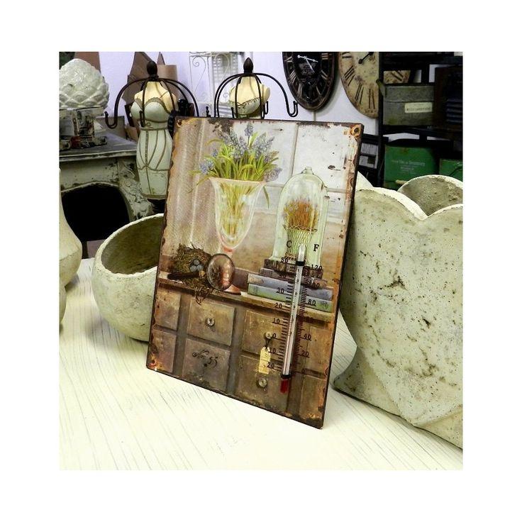 Termometr znajdujący się na obrazie przedstawiającym komodę na której leżą książki i stoją kwiaty w wazonie. Motyw ten ukazuje styl prowansalski. Idealna dekoracja na przykład do salonu.