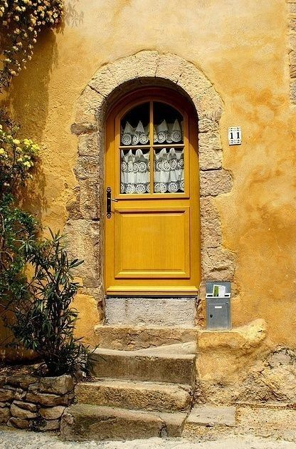 Yellow door with stone archway