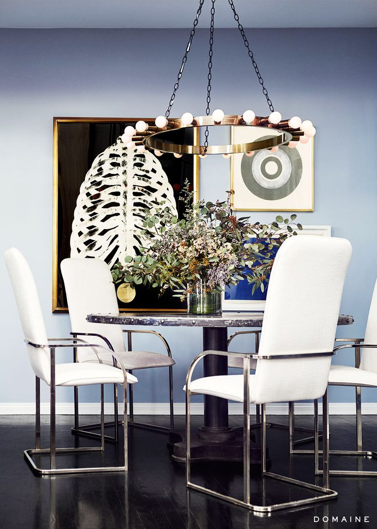 White chairs around dining table with floral arrangement, modern light fixture, and small gallery wall