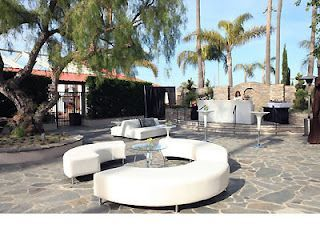 A beautiful cocktail event in Newport Beach, CA. In the furthest view of this photo you will see our light-up bars with a row of white bar tables and stools adjacent to it. You will also notice our modular sofas back to back and our semi-circle ottomans. All of this furniture can be found at www.modernchairrental.com