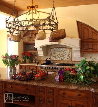 This Tuscan Italian style kitchen was designed by Maraya with an arch over the stove area, and a plaster hood to give it an old world charm. The pot rack is custom wrought iron, as are the old style cabinets. (Note: I MUST have a mosaic backsplash mural in my kitchen just like this one!)
