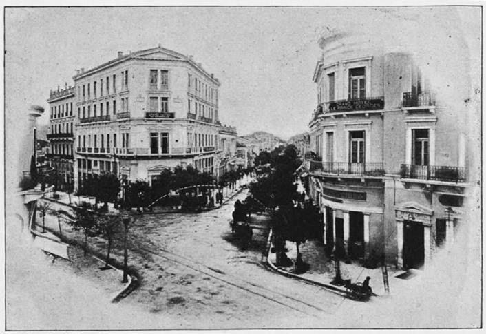 Μετά το ξενοδοχείο Απόλλων, φαίνεται το νεοκλασικό με το καφενείο Παρθενών, τις μαρμάρινες στήλες στους εξώστες, το άγαλμα στην κόγχη.
