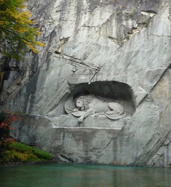 Dying Lion Monument / Lucerne, Switzerland. A giant lion carved out of a wall of sandstone rock serves as a memorial for the soldiers from Switzerland who lost their lives during the French Revolution.