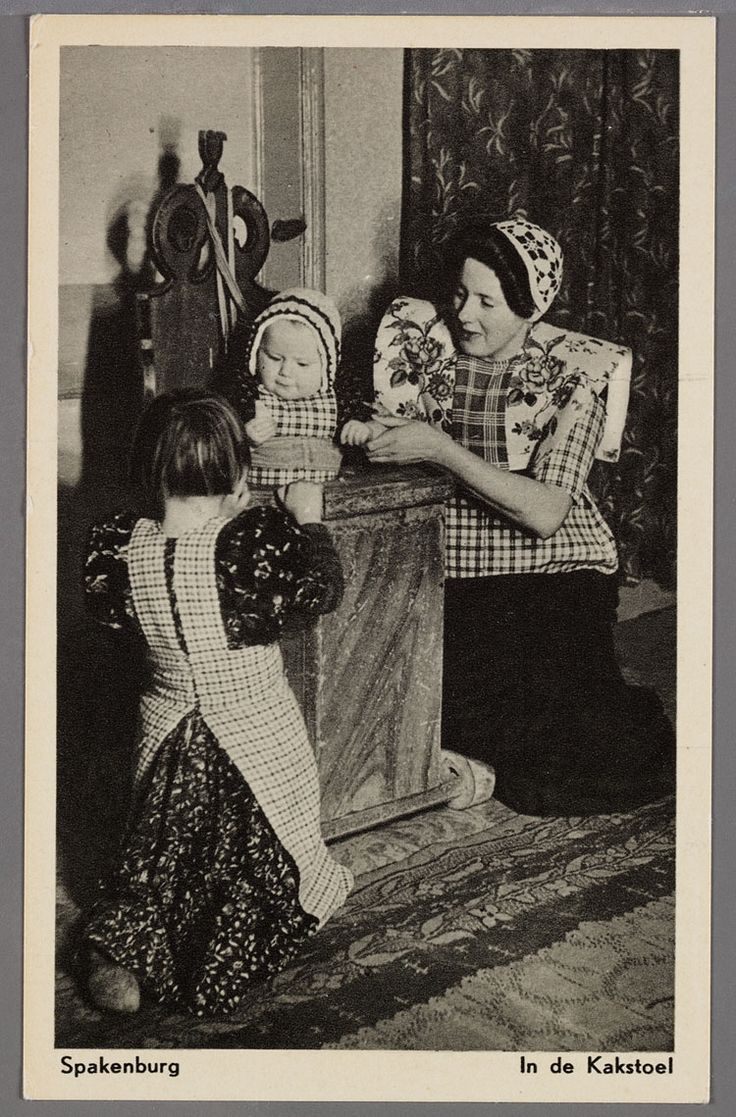 In de Spakenburgse kinderstoel (kakstoel) een kind met doopmutsje, jurkje en fries schort, vastgebonden met leidsels. Links een meisje in jurkje en fries schort, van achter gezien, rechts een vrouw met gehaakte muts met kuif, gebloemde kraplap en gedeelde rode doek, geruite boormouwtjes en bovenstukje aan schort. 1950-1960 #Utrecht #Spakenburg