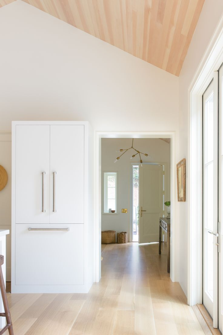 Inside, the house seems to expand: with soaring ceilings and a clever room layout, it feels far larger inside than it seems from the outside. Here, the entryway leads directly into the kitchen. Note the custom-builtcabinet that conceals the fridge and adds to the vintage feel.