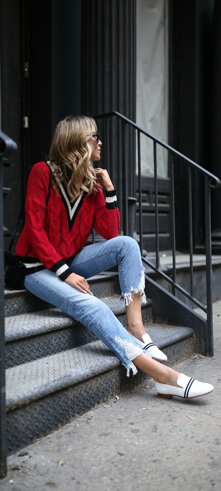 Top 10 Spring Trends to Know // How to Wear Trend #6: Athletic-Inspired Varsity Vibes // click the image for all the details! // red v-neck cableknit sweater with black and white striped detailing, ripped frayed hem high waisted boyfriend jeans, white loafers with black and white strip ribbon detail, ysl bag // 3x1 denim, rag and bone style