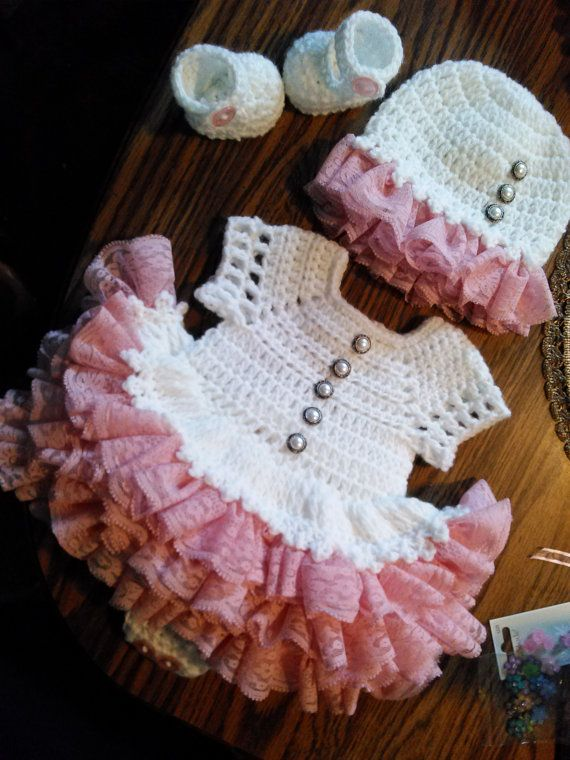 white crochet baby onsie dress with pink lace ruffles.