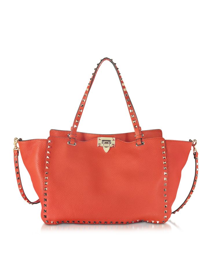 Rockstud Deep Coral Leather Medium Tote crafted in supple calf leather with signature pyramid stud detailing, adds mood with emotional hues and an edge to your look. Featuring the signature platinum pyramid stud detailing, detachable adjustable leather studded shoulder strap, flip lock closure and on trend trapeze shape for all the room you need to carry the essentials. Signature dust bag included. Made in Italy.