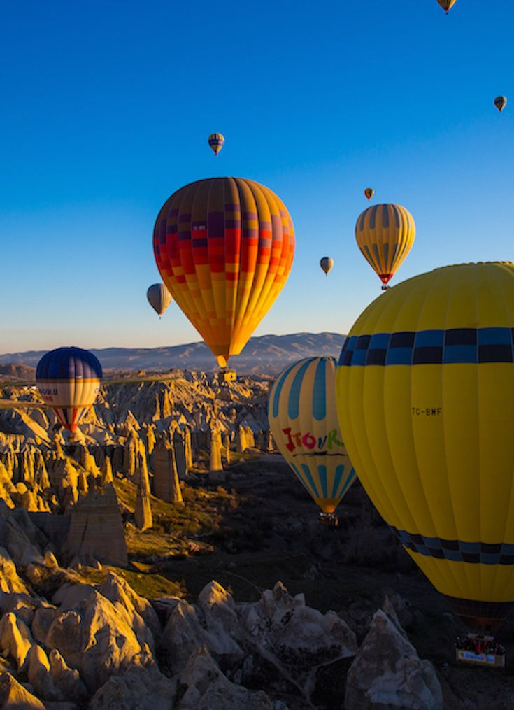 Hot Air Ballooning in Cappadocia Turkey:  It's not only the experience of floating above other-worldly landscapes, but the magical experience of being in the midst of dozens of other balloons greeting the morning light with you. See more at http://BlueSkyTraveler.com