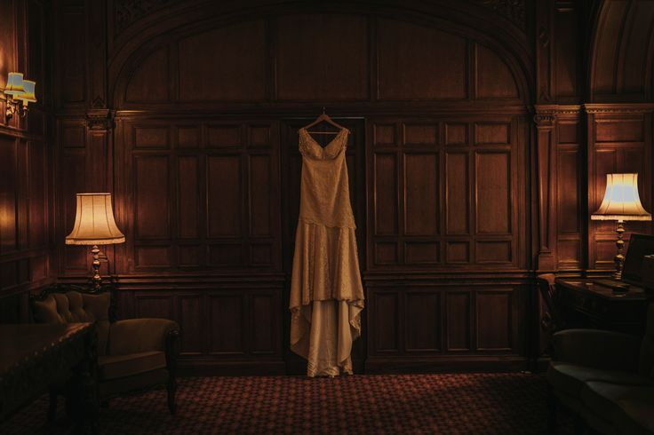 There's something classic about this lovely wedding dress hanging in front of wood panelling in this beautiful low light. Photo by Benjamin Stuart Photography #weddingphotography #weddingdress #bride #weddingday #hangingdress