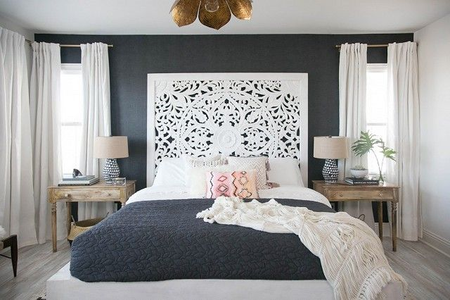 Bohemian inspired bedroom with gray wallpaper and a large intricate white headboard