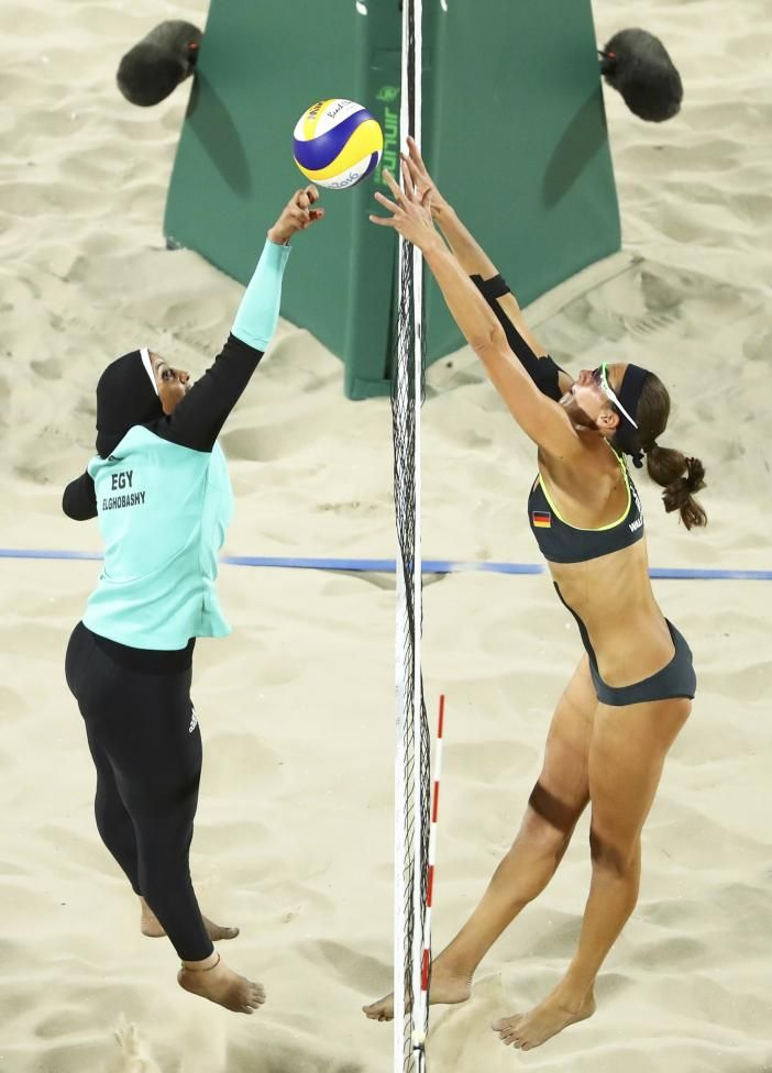 Doaa Elghobashy of Egypt and Kira Walkenhorst of Germany compete int he preliminary beach volleyball event. REUTERS/Lucy Nicholson