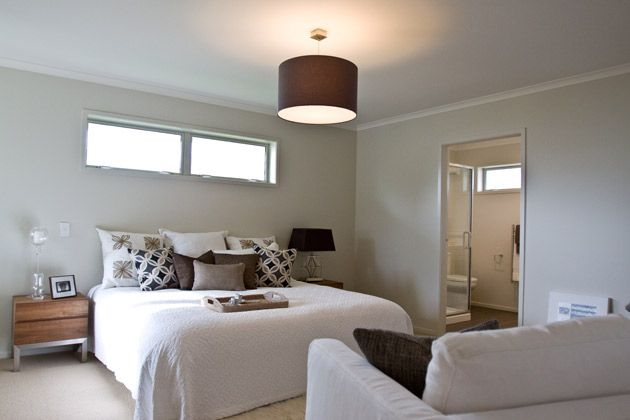 This bedroom has the lovely long window above the bed, giving plenty of light into the room. The central light with a lampshade covering brings warmer tones to the room. #ClassicBuiders #newhomes #softfurnishings