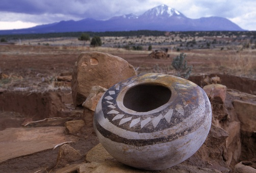 An ancient pottery seed jar and Sleeping Ute mountain in the distance.  Location:	Mesa Verde, Colorado.