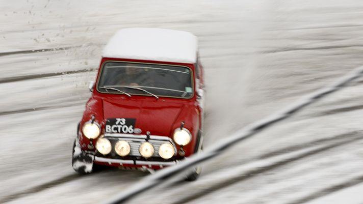 A classic Mini Cooper plays in the snow.