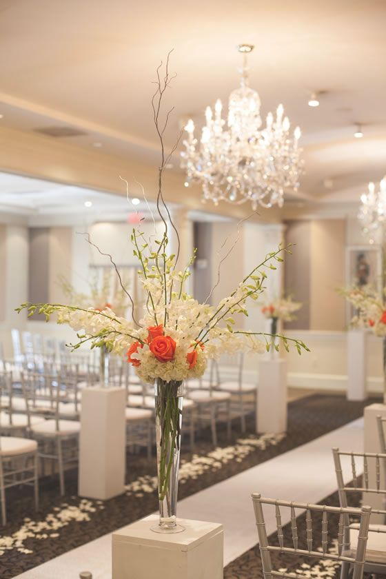 Tall Minimalist Vases Of White Orchids Anchored With Orange Rosebuds On Simple Rectangular Pillars Wedding Ceremony