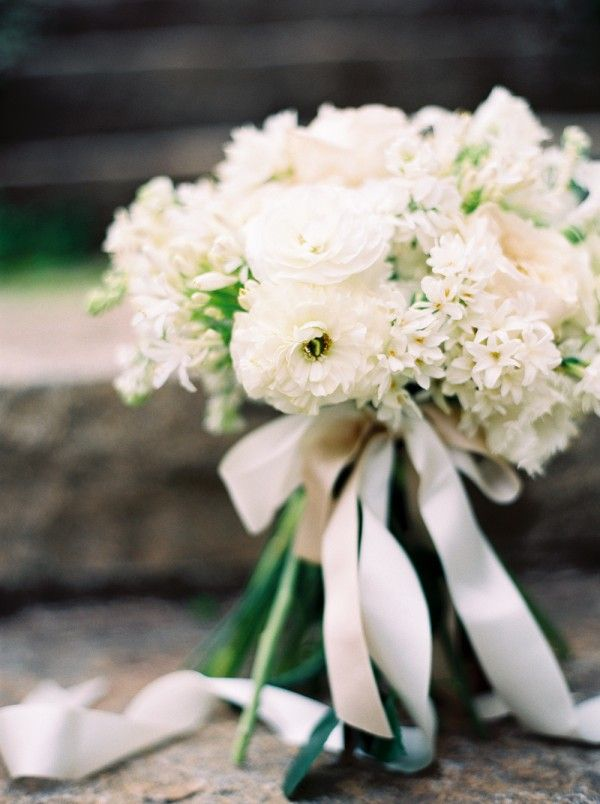 Spring white wedding bridal bouquet with ranunculus, garden roses, hyacinth, paper whites, agpanthus, fringe tulip, lilac, stock, and sweet pea