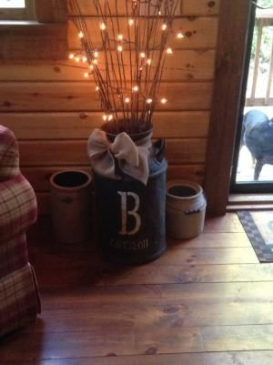 Old Milk Can With Lighted Twigs & decorated with a Burlap Ribbon and Initial. Looks great on the hardwood floor and with the pottery pieces here.  by: nikki