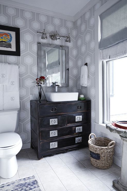 Stunning bathroom with gray hexagonal wallpaper framing a black Asian style chest finished with a rectangular basin sink