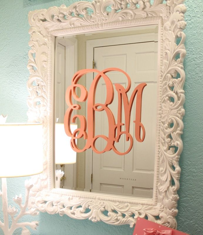baby's initials painted coral on a framed mirror in an aqua blue nursery
