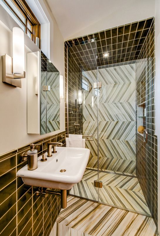 luxe bath outfitted in chevron cut marble and handmade ceramic subway tiles that wrap the walls