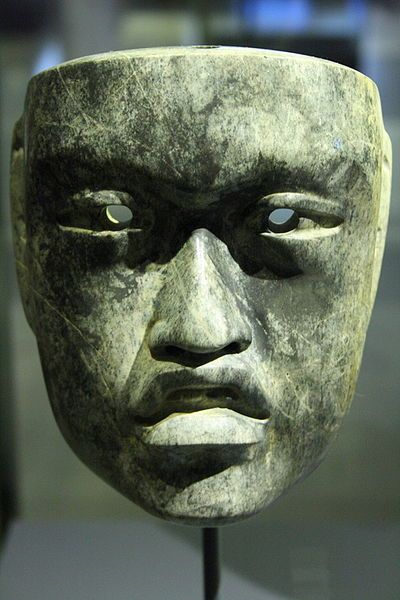 The object is carved from serpentine, a dark green stone, commonly used in Olmec artwork. Making an assumption from its small size, the object was most likely worn as a necklace rather than a mask. The face is probably a replica of an Olmec king. The Olmec people are more well-known for the colossal stone heads depicting their kings.