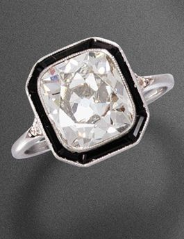 ONYX AND DIAMOND RING, CIRCA 1925. Set with a cushion cut diamond weighing 2.60 carats, surrounded by calibré-cut onyx, and mounted in platinum