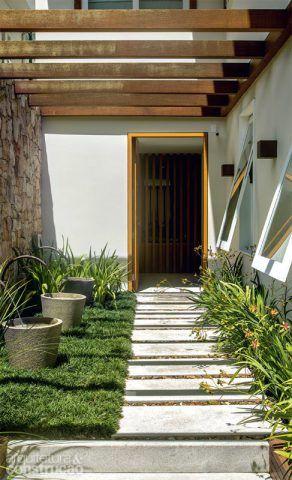 No corredor que leva à porta social, placas de granito Aqualux serrado (20 x 70 cm) foram entremeadas a seixos. Projeto do arquiteto Erick Figueira de Mello.