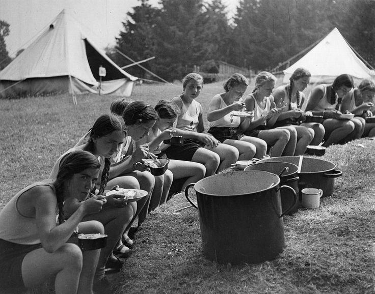 """Reinwarzhofen. Zeltlager des Bundes Deutscher Mädel (BdM) auf dem Zeltlagerplatz """"Göring-Espan"""". Mädchengruppe in Sportbekleidung, im Kreis auf sitzend und im Freien essend - Deutsche Digitale Bibliothek"""