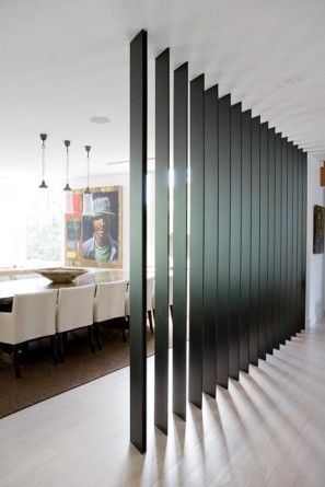 Modern family home with touches of the Moroccan and Asian Influence. The metal blade wall through the centre of the living space provides both a practical function of separating spaces and a beautiful feature which throws light deep into the plan.