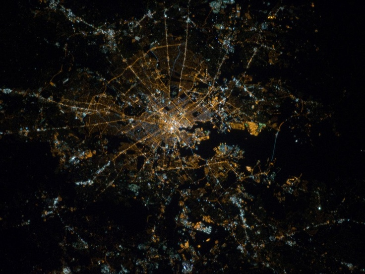 Baltimore, Maryland. The most brightly lit area corresponds to the highest density of buildings and typically indicates the urban core – in this case, downtown Baltimore at center. Highways and large arterial streets appear as bright yellow-orange lines extending outwards from the downtown area into the surrounding suburban regions. Dark areas beyond the suburban zone are rural, dark zones within the metropolitan area are open spaces including parks, cemeteries, and the Baltimore Zoo.